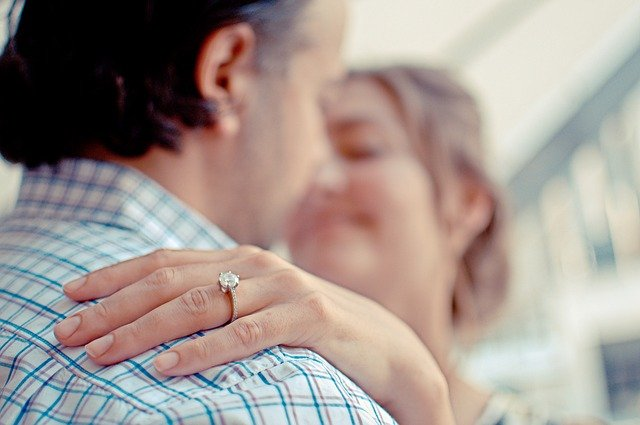 婚約指輪を着けて男性の肩に手をのせる女性