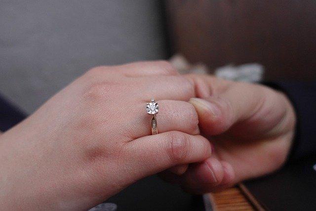 婚約指輪を着けたと女性と、手を握る男性