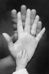 子どもと指輪を着けた親が手を重ね合うシーン