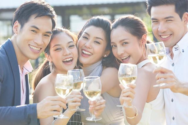 グラスを持って笑顔で乾杯している男女